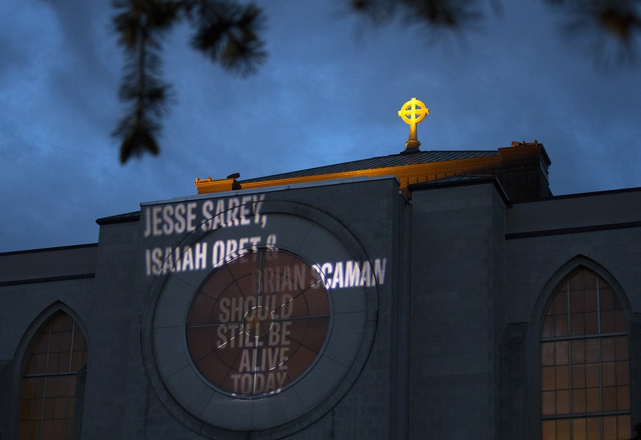 """caption: 'Jesse Sarey, Isaiah Obet & Brian Scaman Should Still Be Alive Today' is shown projected onto the side of Saint Mark's Episcopal Cathedral on Thursday, June 3, 2021, in Seattle. The """"Projecting Justice"""" project is a collaboration between the ACLU of Washington, The Washington Coalition for Police Accountability, and Saint Mark's. On Thursday, family members of those killed by Auburn police officer Jeffrey Nelson gathered for a small vigil."""