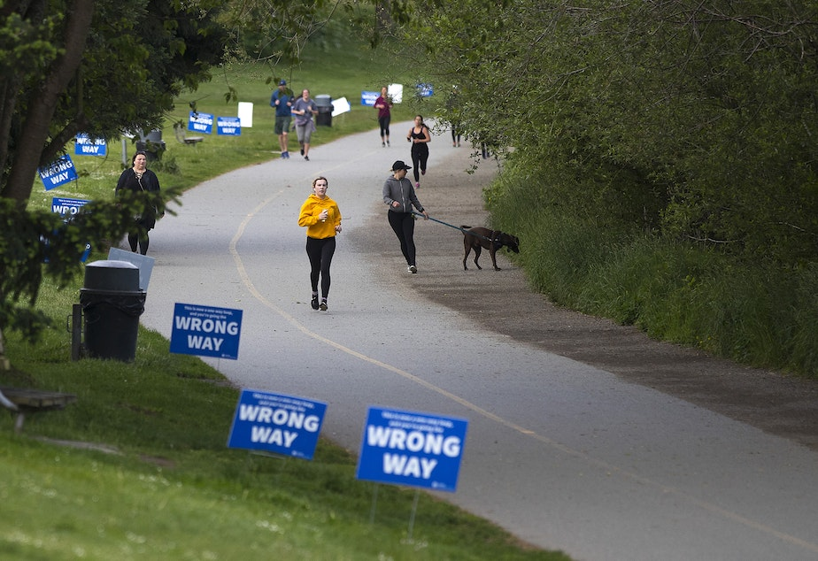 caption: People walk and jog around the perimeter of Green Lake on Monday, May 18, 2020, the same day that King County's new face covering directives go into effect, in Seattle.