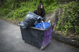 Ethan Kent, 26, uses a cart to transport his belongings as well as the belongings of friends away from a Ravenna encampment where he had been living for roughly a month and a half, on Wednesday, April 18, 2018, on the Burke-Gilman Trail in Seattle.