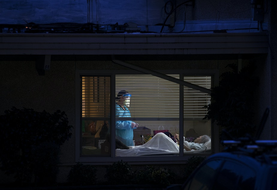 caption: A health worker talks with Susan Hailey, 76, in her room at the Life Care Center of Kirkland, on Friday, March 13, 2020, in Kirkland.