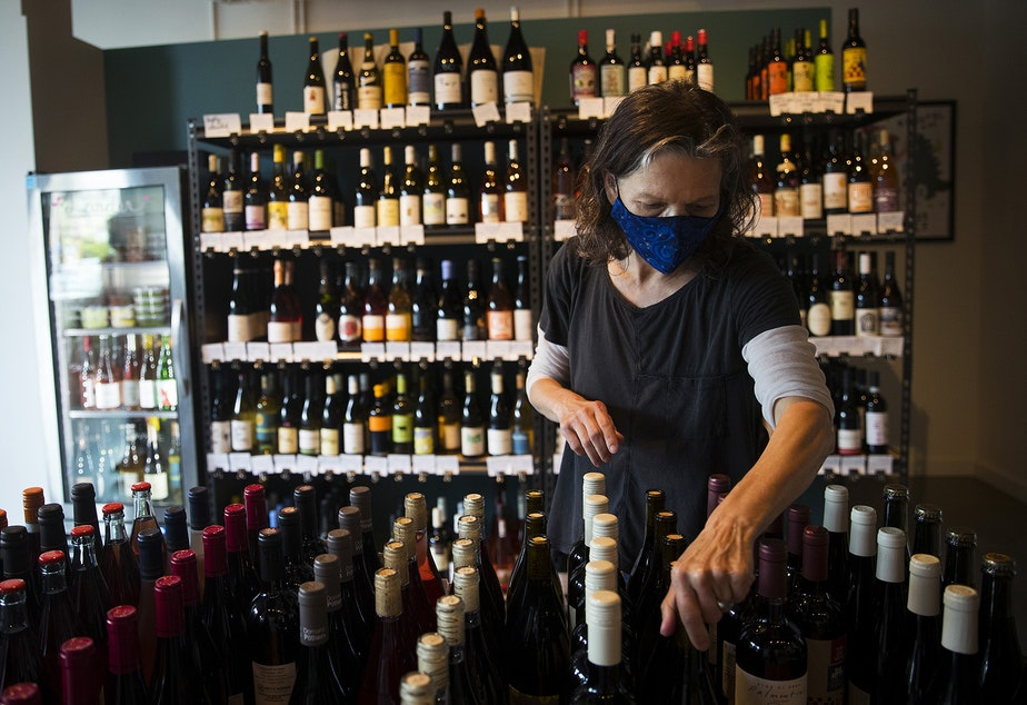 caption: Co-owner of Petite Soif Shawn Mead arranges wine bottles on Thursday, July 16, 2020, in Seattle.