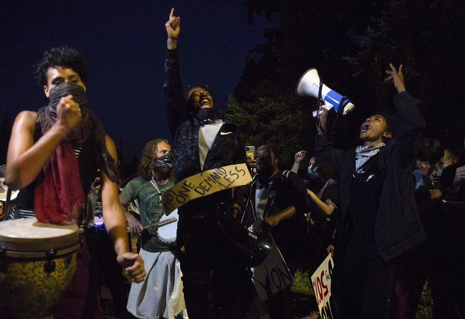 caption: Organizers of the Everyday March, Tealshawn Turner, also known as TK, center, and Katie Neuner, dance along to the EDM Band while marching on a public street toward Seattle City Councilmember Debora Juarez's home in an effort to have a dialogue about racial justice and police brutality on Tuesday, August 4, 2020, in Seattle. Councilmember Juarez did not come outside and the group spoke with the councilmember's daughter Memphis instead.