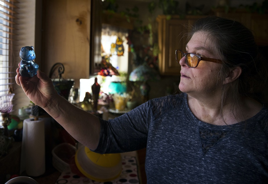 caption: Dagmar Devere holds a Fenton bear up to the light on Tuesday, April 23, 2019, at her home near Pateros, Washington. Devere lost everything, including her home, in the Carlton Complex Fire, and the Fenton bear was the only thing that survived.