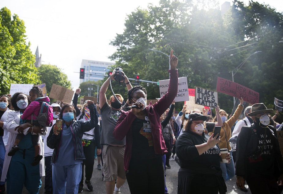 caption: Organizer Dr. Estell Williams, center, leads a crowd of thousands marching in protest to demand justice and an end to police violence, from Harborview Medical Center to Seattle City Hall on Saturday, June 6, 2020, in Seattle.