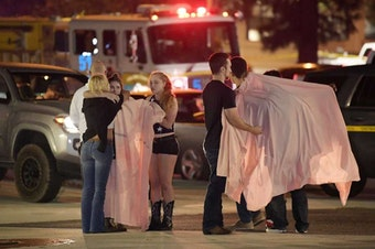"""People comfort each other as they stand near the scene Thursday, Nov. 8, 2018, in Thousand Oaks, Calif. where a gunman opened fire Wednesday inside a country dance bar crowded with hundreds of people on """"college night,"""" wounding 11 people including a deputy who rushed to the scene."""