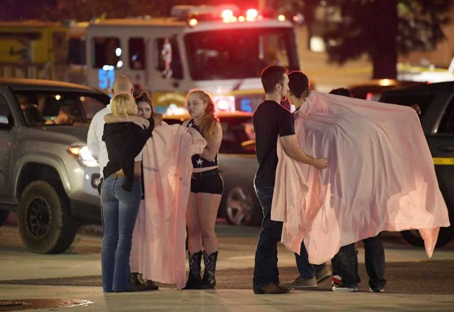 "People comfort each other as they stand near the scene Thursday, Nov. 8, 2018, in Thousand Oaks, Calif. where a gunman opened fire Wednesday inside a country dance bar crowded with hundreds of people on ""college night,"" wounding 11 people including a deputy who rushed to the scene."