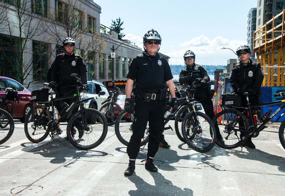 caption: FILE: Seattle police officers observe marchers moving down 4th Avenue during the Black Lives Matter rally in Seattle, Saturday April 15, 2017.
