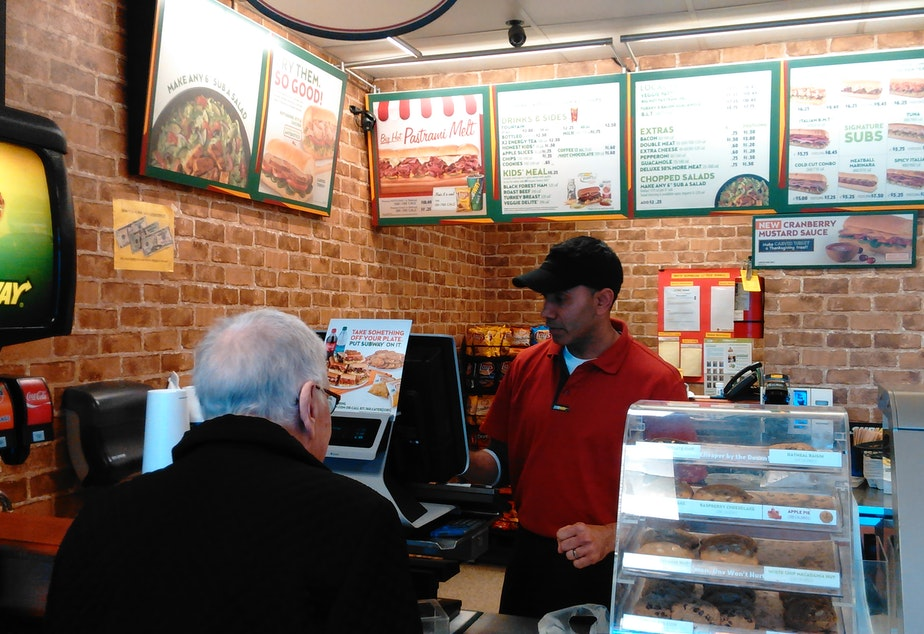 caption: Karam Maan says his Subway franchise has been hit hard by wage increases in Seattle
