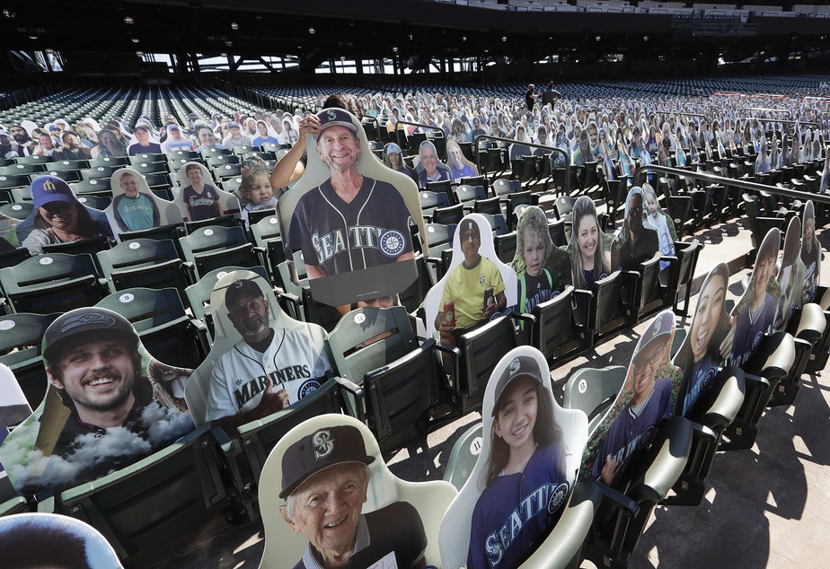 "caption: A Seattle Mariners worker places a fan cutout in a seat at the team's ballpark as part of the ""Mariners Seat Fleet"" in place of real fans, Monday, July 27, 2020, in Seattle. The Mariners open play at home against the Oakland Athletics on Friday."