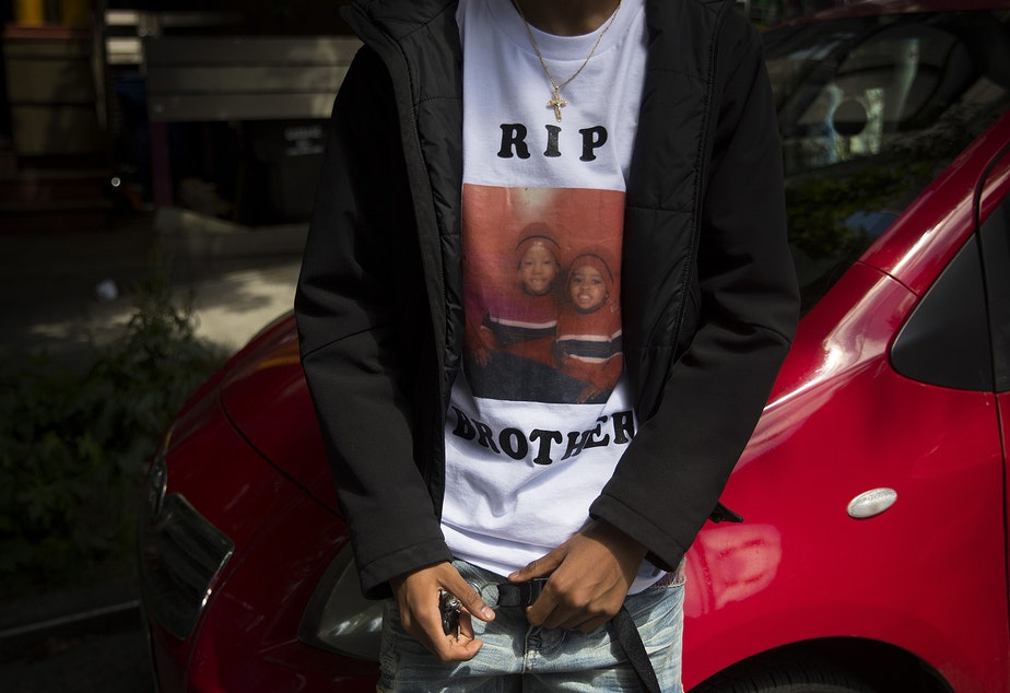 caption: The 17-year-old brother of 19-year-old Horace Lorenzo Daeshawn Anderson, who was shot and killed outside of the Capitol Hill Organized Protest zone on June 20, wears a t-shirt with an image of the two of them as children, on Monday, June 29, 2020, in Seattle.