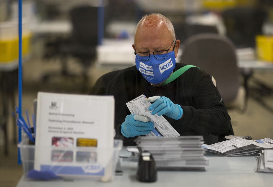 caption: An elections worker removes ballots from envelopes on Wednesday, October 28, 2020, at King County Elections in Renton.