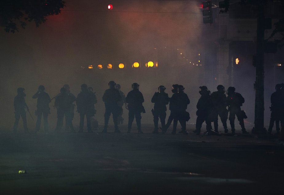 caption: FILE: Seattle police officers dressed in riot gear stand in a cloud of chemical agents and pepper spray  on the fifth day of protests following the violent police killing of George Floyd on Tuesday, June 2, 2020, at the intersection 11th and Pine Street in Seattle.