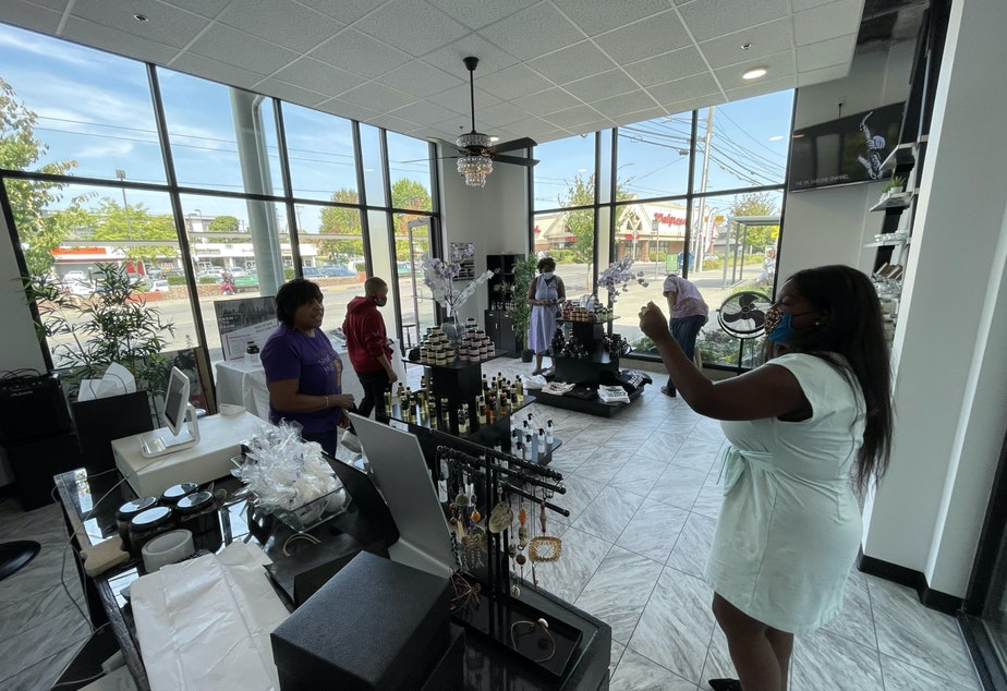 caption: At Queencare, Monika Mathews jokes with customers as they browse the store.