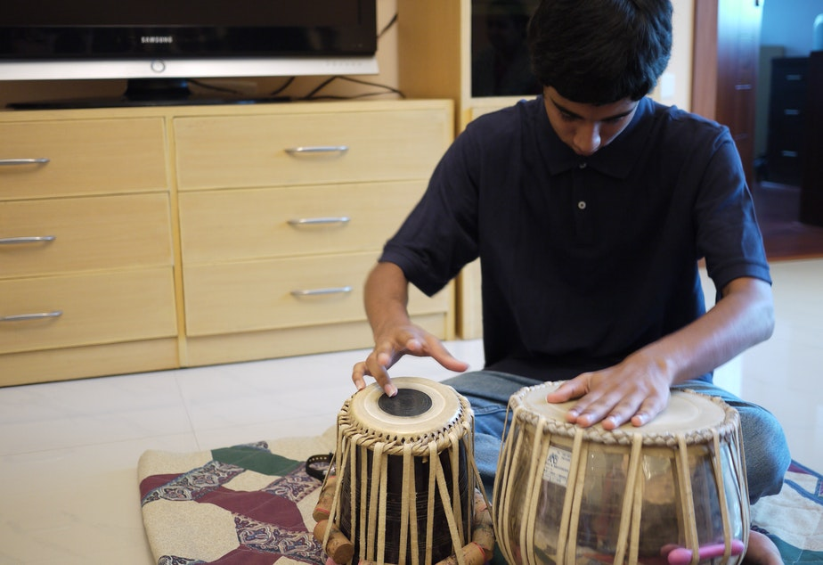 caption: Apurva Koti, 16, plays tabla drums in his living room in Hyderabad, India.  Apurva also plays electric guitar. Apurva and his family moved to India from Redmond, Washington in 2008.