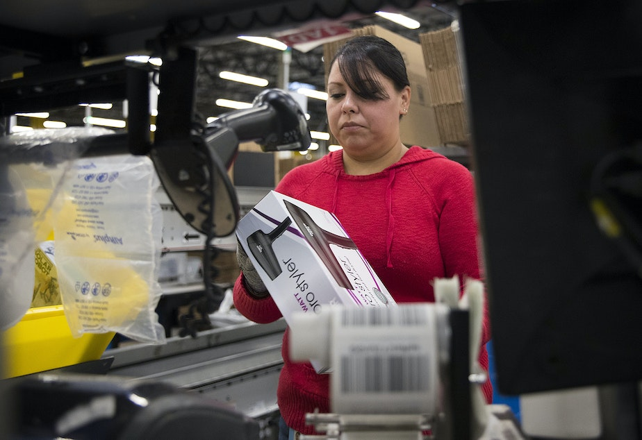 caption: Clara Vazquez scans items before putting them into boxes at an Amazon fulfillment center on Friday, November 3, 2017, in Kent.