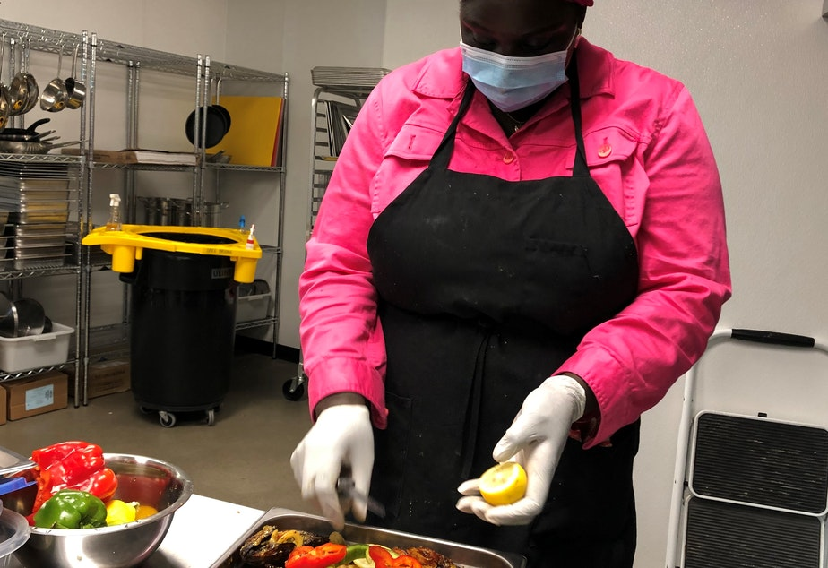 caption: Oumie Sallah puts a finishing touch to Fish Yassa, a dish native to Gambia, her home country.