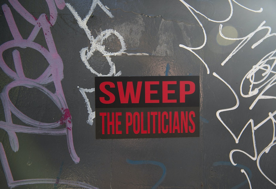 caption: A sticker that reads 'Sweep The Politicians' is shown near Denny Park as unhoused people are swept from the area by the city of Seattle, on Wednesday, March 3, 2021.