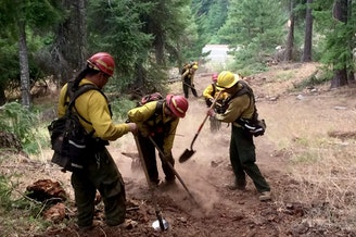 Firefighter Judy Hoffman helps dig line to stop a wildfire. CREDIT: JUDY HOFFMAN