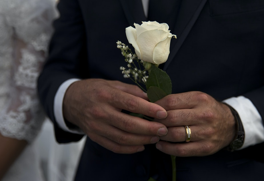 caption: Himmbler Bernal holds a white rose while standing next to his wife, Lucelba, during a mass wedding ceremony on Sunday, June 2, 2019, at Our Lady of the Desert Church in Mattawa.
