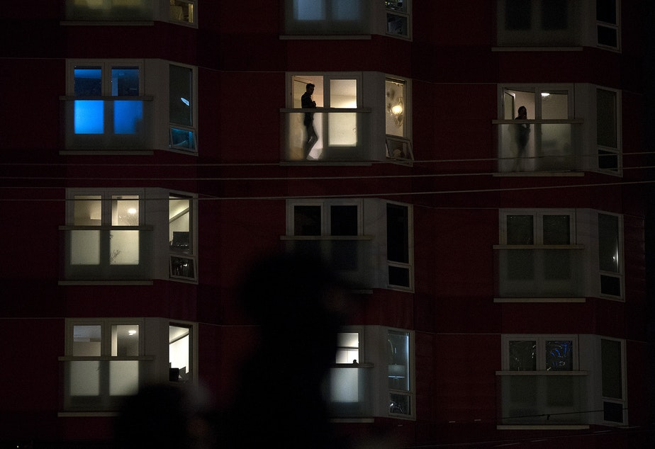 caption: People watch from their apartment windows as multiple groups of people gather together at Cascade playground before marching for Black lives and against police brutality on the night of the 2020 presidential election, on Tuesday, November 3, 2020, in Seattle.