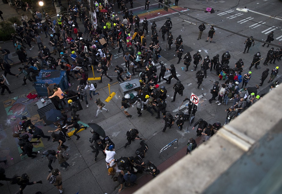 caption: Seattle Police officers run toward people protesting for racial justice and against police brutality before making arrests at the intersection of 11th Avenue and East Pine Street following the Youth Liberation Front march in solidarity with Portland, on Saturday, July 25, 2020, in Seattle.