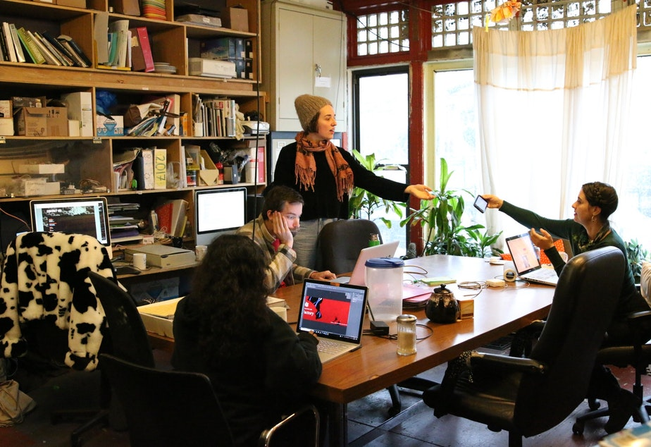 caption: Staff at Flux Factory in Queens New York have concerns about Amazon's arrival. Here, they work on a grant application.