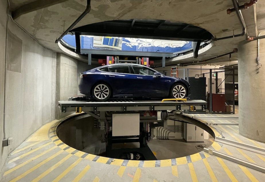 caption: A car on a piston at the robotic parking garage in the Spire