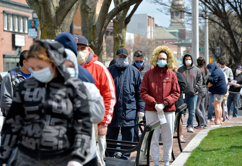 caption: People wait in line to get food distributed by the National Guard in Chelsea, Mass., on April 16. Harvard researchers found areas with more poverty, people of color and crowded housing had higher mortality rates for the coronavirus.