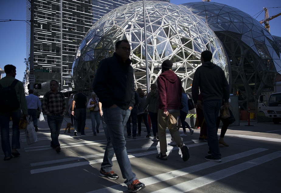 A crowd is showing crossing the street in front of Amazon's biospheres during Amazon's bring your parents to work day on Friday, September 15, 2017, in Seattle.