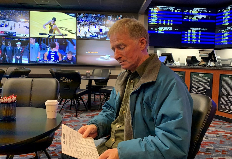 caption: Football and basketball fan David Salisbury studying the daily odds at the Chinook Winds Casino sportsbook in Lincoln City, Oregon.