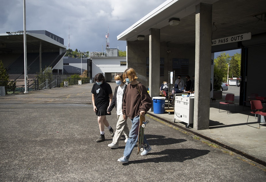 caption: Students at The Center School from left, Oskar, Dakota and Clem, walk toward the observation area after Clem, right, received a dose of the Pfizer Covid-19 vaccine from Seattle Fire Department Captain Melissa Woolsey, on Tuesday, May 18, 2021, at Memorial Stadium in Seattle.