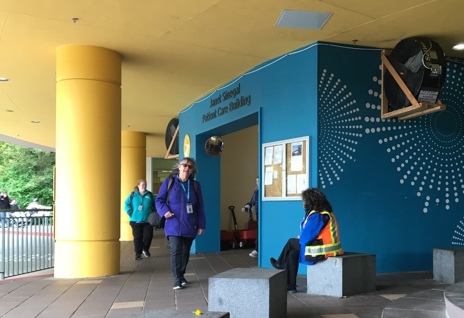 """caption: Giant fans push air away from an entrance to Seattle Children's Hospital. A sign on the fans says, """"Please keep fans on during weekday construction hours."""""""