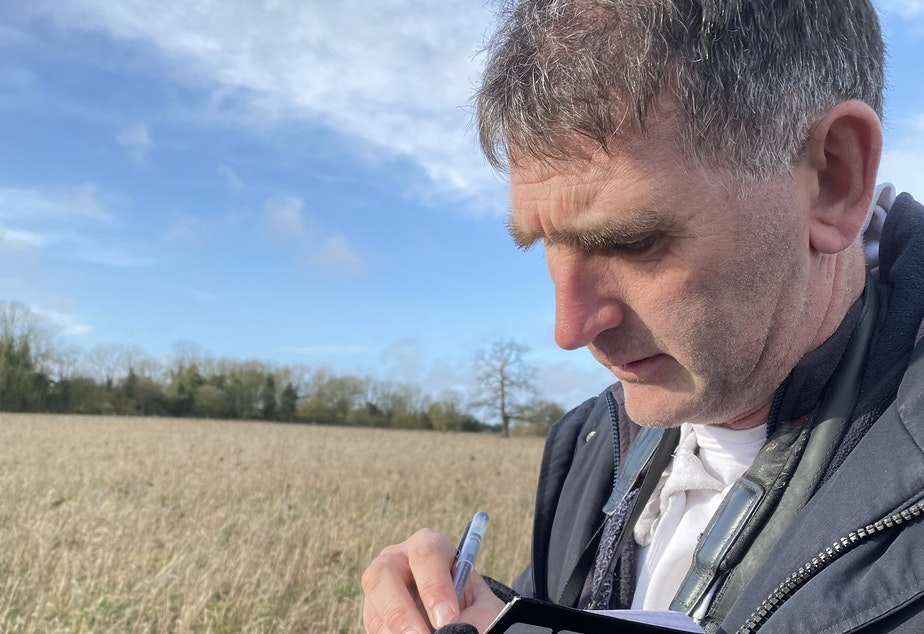 caption: Twitcher Lee Evans marks down his latest bird find in his notebook. He's identified 594 different bird species through the UK and Ireland.