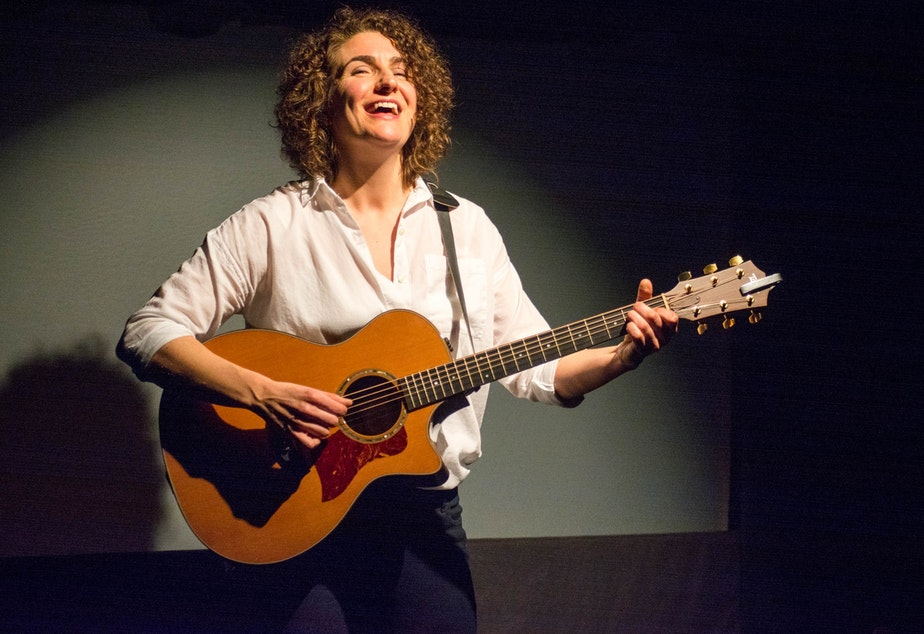 caption: Bridget Quigg plays guitar on stage during her one-woman show 'Techlandia.'