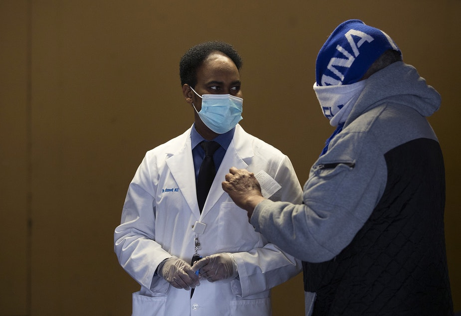 caption: Dr. Ahmed Ali, Executive Director of the Somali Health Board, left, talks with a community member who is set to receive their first dose of the Moderna Covid-19 vaccine, on Wednesday, February 3, 2021, at the Brighton Apartments complex on Rainier Avenue South in Seattle. The Othello Station Pharmacy provided 100 doses of the vaccine for seniors at the clinic.