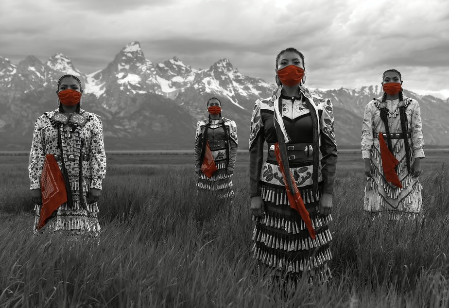 caption: Erin and Dion Tapahe, far left and right, and Sunni and JoAnni Begay, center, pose with red masks and scarves. The scarves pay homage to missing and murdered indigenous women.