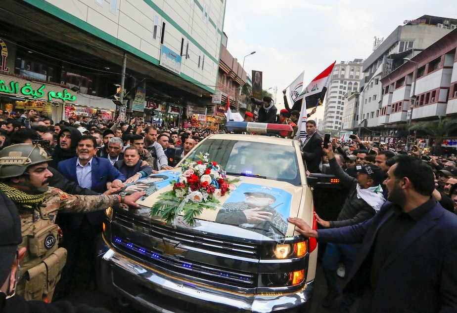 Mourners surround a vehicle carrying the coffins of Iranian Maj. Gen. Qassem Soleimani and Iraqi militia leader Abu Mahdi al-Muhandis, during a funeral procession Saturday in Baghdad. Both men were killed in a U.S. airstrike near the Iraqi capital's airport earlier this week.