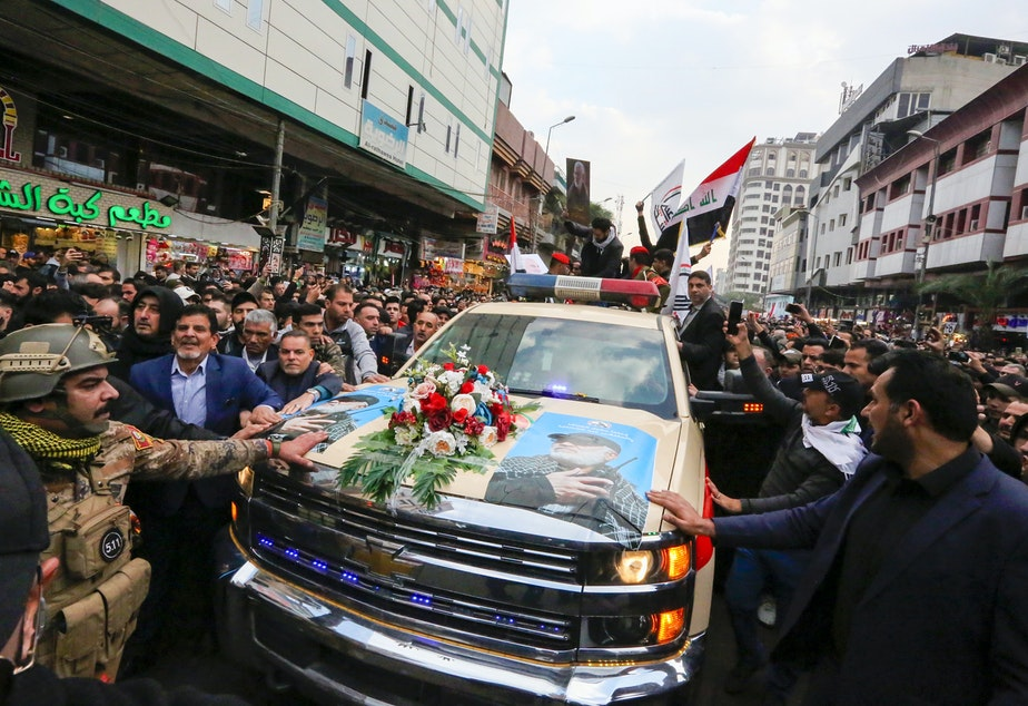 caption: Mourners surround a vehicle carrying the coffins of Iranian Maj. Gen. Qassem Soleimani and Iraqi militia leader Abu Mahdi al-Muhandis, during a funeral procession Saturday in Baghdad. Both men were killed in a U.S. airstrike near the Iraqi capital's airport earlier this week.
