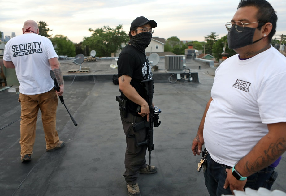 caption: Armed volunteers take up rooftop positions in a Minneapolis neighborhood; those who are not allowed to carry guns are kept off the roof.