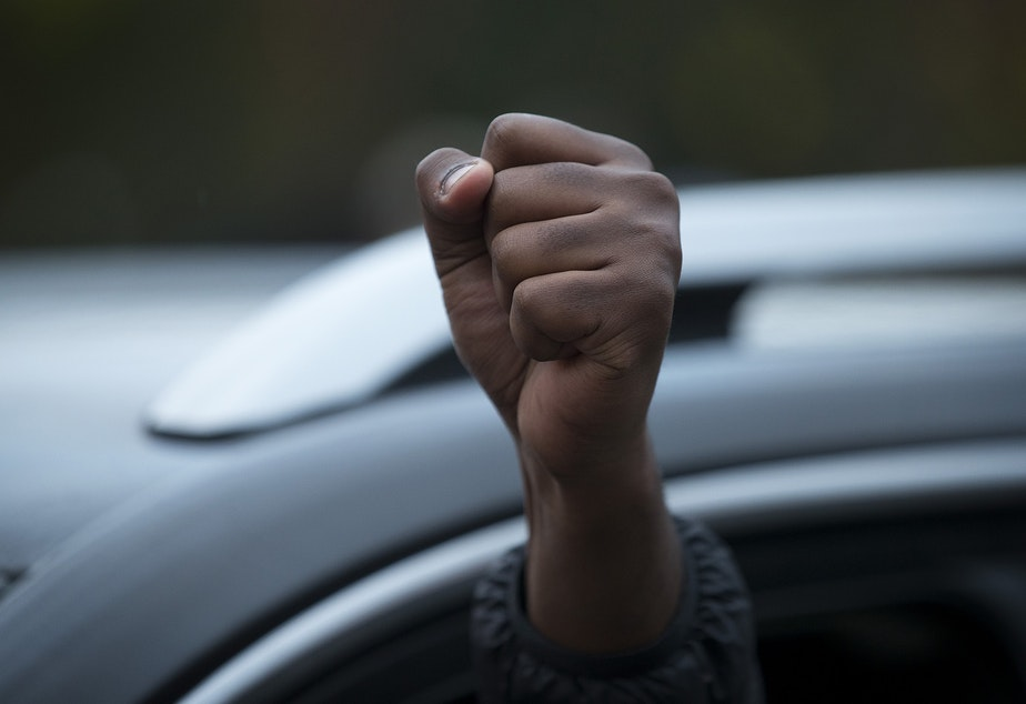 caption: A driver raises their fist in the air while passing a large gathering of hundreds celebrating after Joe Biden was officially named the president elect on Saturday, November 7, 2020, at the intersection of 10th Avenue and East Pine Street in Seattle.