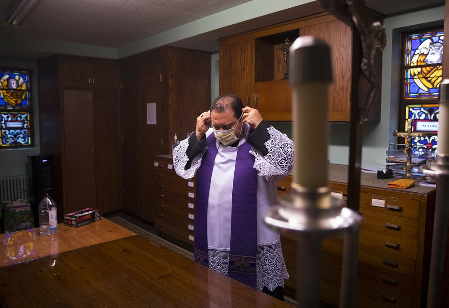 caption: Father Jose Alvarez puts on a mask before walk and drive through confessions on Friday, April 24, 2020, at Holy Family Roman Catholic Church in White Center.