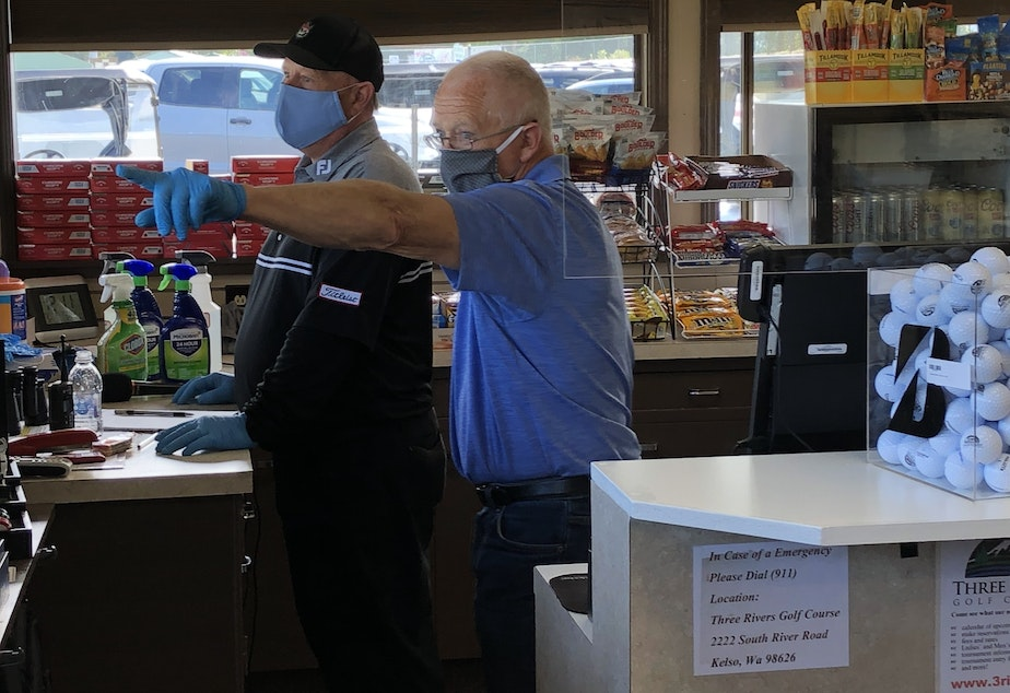 caption: Three Rivers Golf Course general manager Lance Satcher (L) and his desk assistant Randy Wright in the club's pro shop. Washington state allowed its 275 golf courses to reopen this week.
