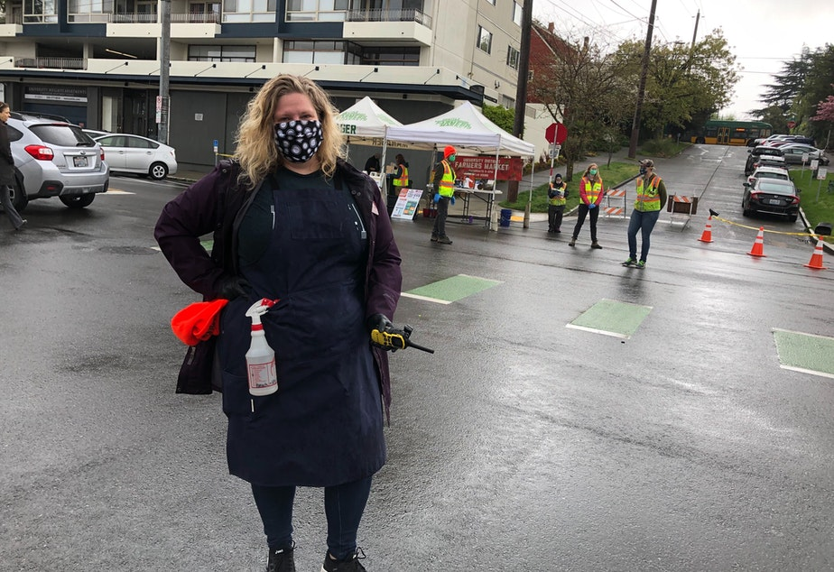 caption: As the U District farmers market reopened, Jennifer Antos limited the number of patrons at one time.