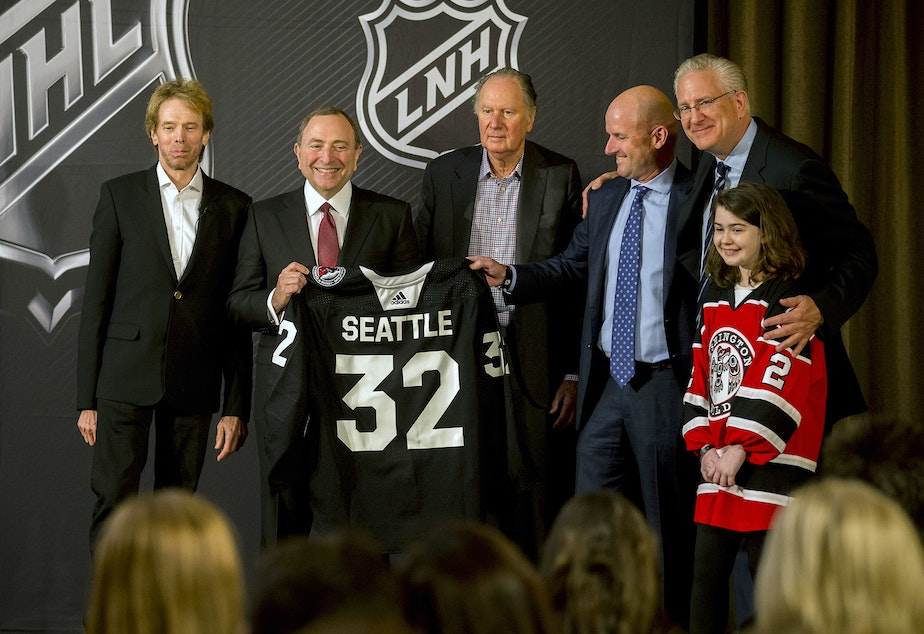 NHL commissioner Gary Bettman (center left) presents a jersey with the number 32, signifying that Seattle is soon to be the NHL's 32nd active franchise. The NHL Board of Governors announced the expansion Tuesday.