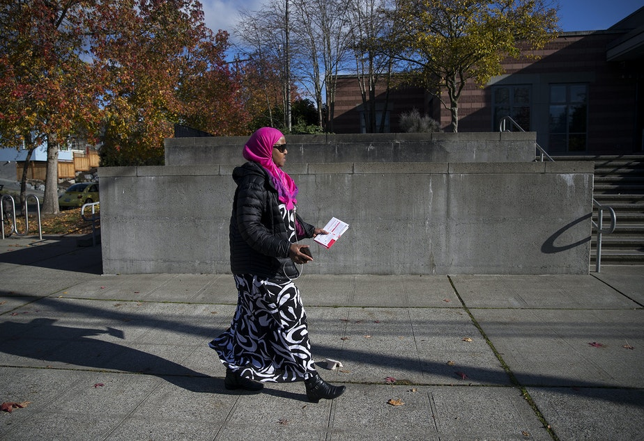 caption: Sadiya Ali walks to the ballot drop box to vote on Tuesday, November 6, 2018, in front of the Rainier Beach Community Center in Seattle.