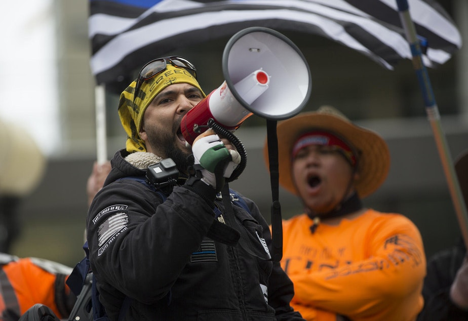 caption: Organizer Joey Gibson of the Vancouver, Washington-based group Patriot Prayer speaks during a pro-Trump rally at Westlake Plaza in downtown Seattle on Monday, May 1, 2017.