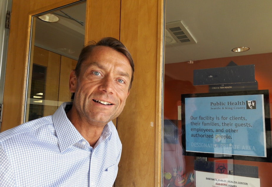TJ Cosgrove stands next to a new sign that greets patients entering Public Seattle-King County's Eastgate clinic.
