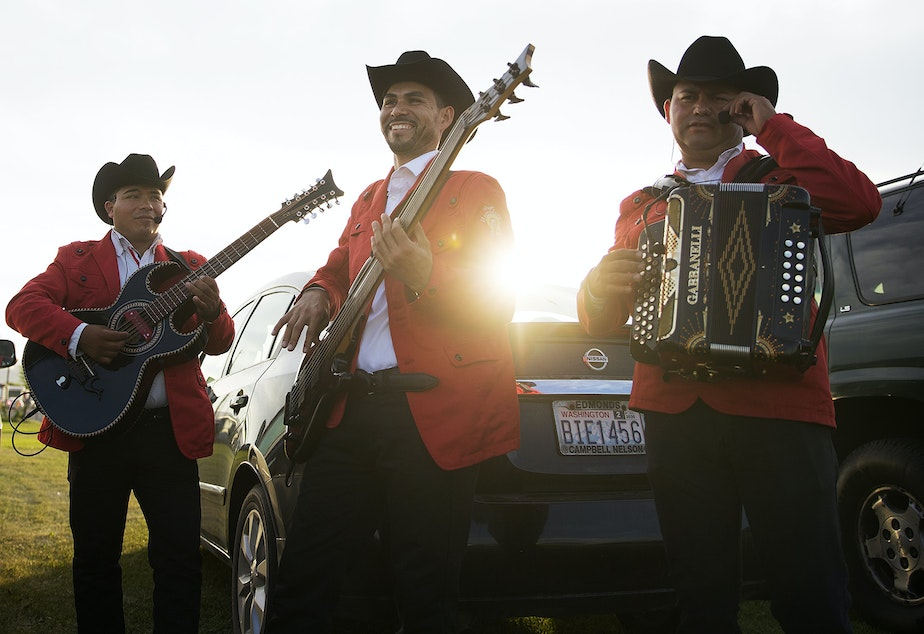 caption: Members of the Grupo Herradura De Plata from left, Fermin Herrera, Everardo Gallardo and Javier Cruz warm up in a parking area before performing during a mass wedding ceremony where 23 couples were married on Sunday, June 2, 2019, at Our Lady of the Desert Church in Mattawa.