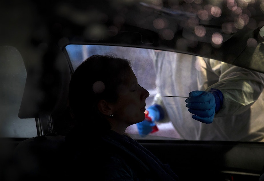 caption: Mark Radford, a paramedic with King County Medic One, administers a Covid-19 test on Wednesday, November 18, 2020, in the parking lot of the Weyerhaeuser King County Aquatic Center along Southwest Campus Drive in Federal Way.