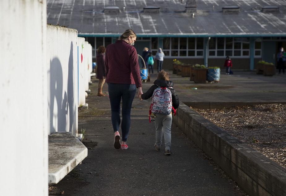 caption: Shelly Kuntz, left, and August Kuntz, right, a kindergarten student at Northgate Elementary School, walk together while holding hands on Monday, April 5, 2021, on the first day of in-person learning at the school in Seattle.
